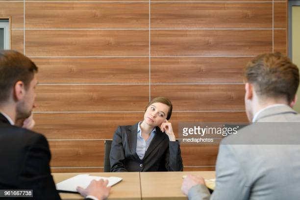 unhappy tired lady boss in formal jacket leaning on armchair handle while listening to subordinates report at meeting in board room - bossy stock pictures, royalty-free photos & images