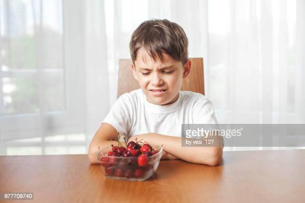 unhappy unenthusiastic boy refuses to eat cherries - afkeer stockfoto's en -beelden