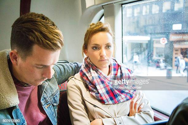 Unhappy upset woman on bus with remorseful boyfriend