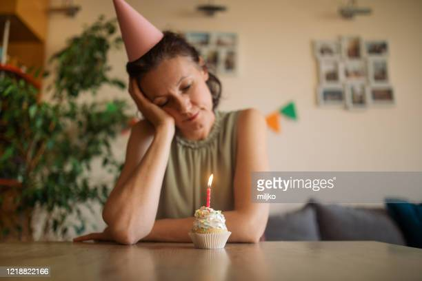 unhappy woman celebrating birthday alone at home - miljko stock pictures, royalty-free photos & images