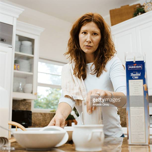 Unhappy woman clearing dishes in kitchen