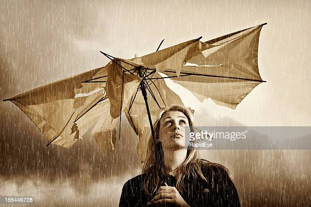 Unhappy woman looks up through frayed umbrella at thunderstorm