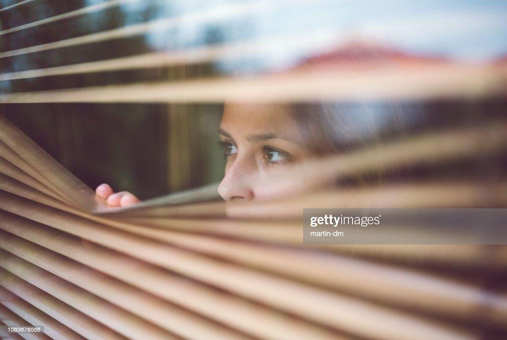 Unhappy woman peeks through the window : Stock Photo