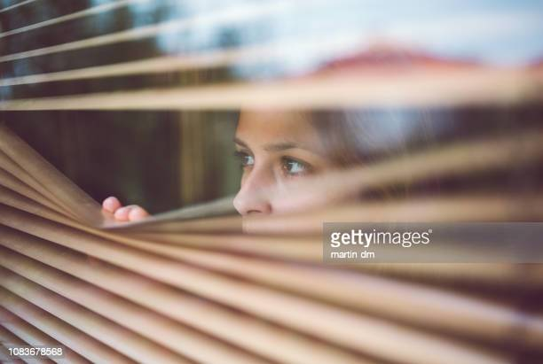unhappy woman peeks through the window - fear stock pictures, royalty-free photos & images