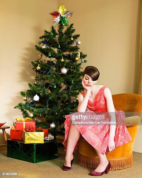 unhappy woman sitting next to christmas tree