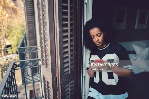 unhappy woman texting at the balcony - distraught stock pictures, royalty-free photos & images