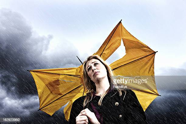 Unhappy young blonde with torn umbrella in thunderstorm
