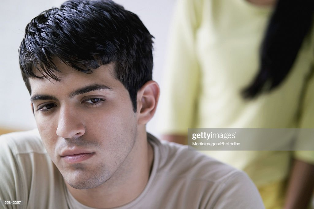 Unhappy young man with unknown woman in background, close-up, selective focus, focus on man : Stock Photo