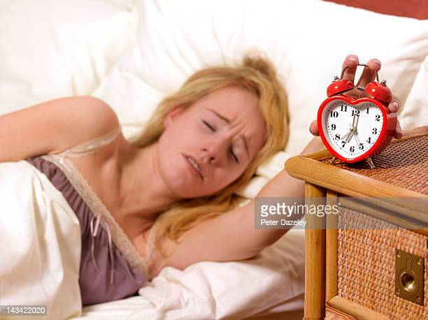 Unhappy young woman being woken up by alarm clock