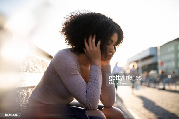 unhappy young woman feeling low - uncomfortable stock pictures, royalty-free photos & images