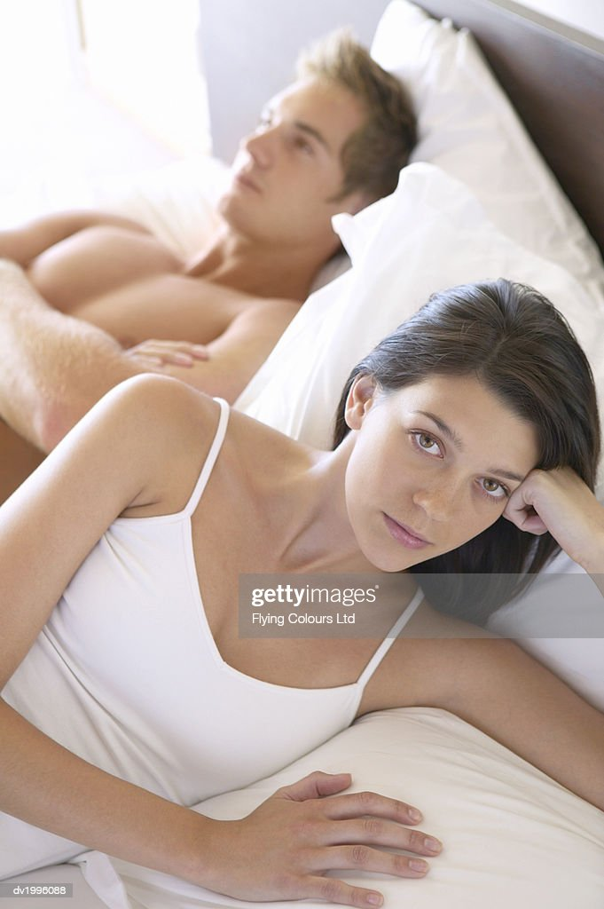 Unhappy Young Woman Lies in Bed Next to a Man Who is Sulking : Stock Photo