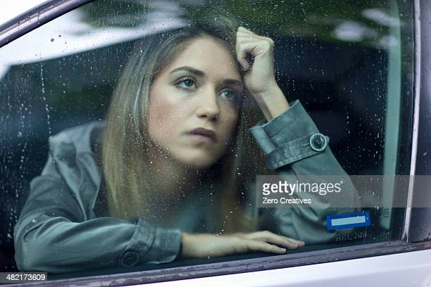Unhappy young woman waiting in car
