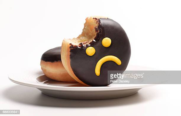 unhealthy doughnut on plate - negative emotion stock pictures, royalty-free photos & images