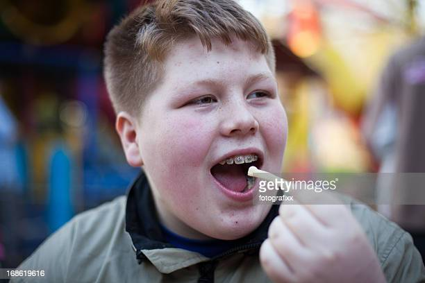 unhealthy eating: redhead overweight teenage boy eats french fries - chubby teen stock pictures, royalty-free photos & images