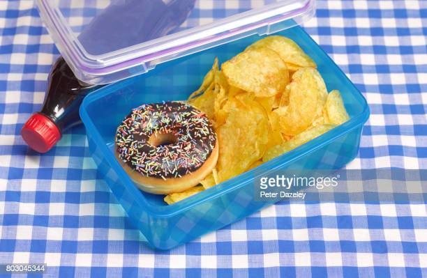 unhealthy lunch box on table cloth - unhealthy living stock pictures, royalty-free photos & images
