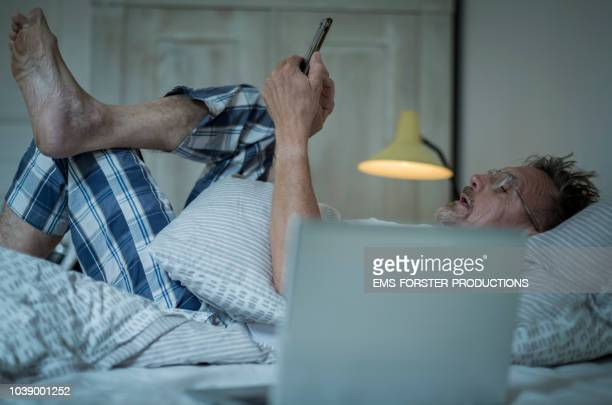 unhealthy senior man in his 60s with greying beard sleepless in bed while night using laptop and smart phone. - varices fotografías e imágenes de stock
