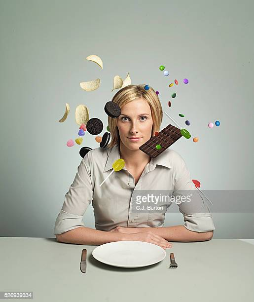 Unhealthy snacks floating around head of woman sitting in front of empty plate