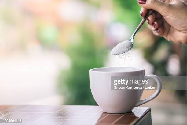 unhealthy woman hand holding spoon pouring sugar in to coffee cup - sucre photos et images de collection