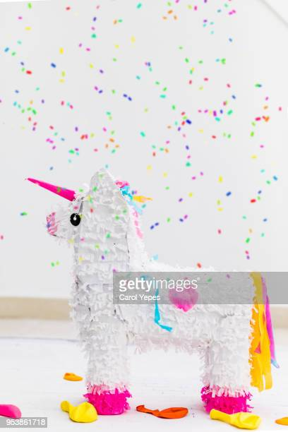 unicorn pinata against white background and confetti falling - pinata stock pictures, royalty-free photos & images