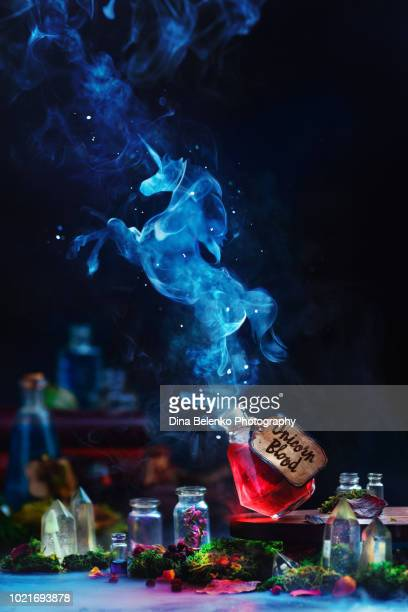 unicorn silhouette made from smoke rising from a red potion bottle. magical still life with witch or wizard workplace, dark background and copy space - potion stock photos and pictures