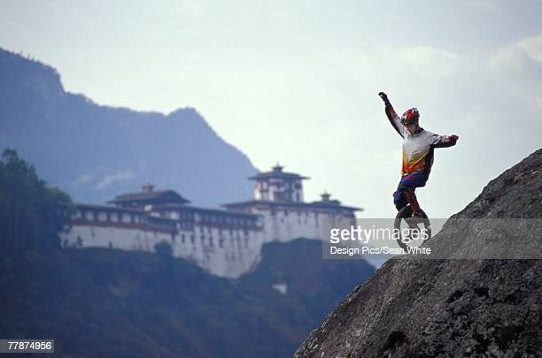 Unicyclist riding down hill with old building in background