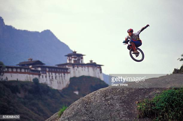 Unicyclist taking jump off hill
