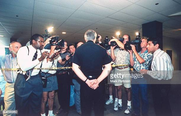Unident male police officer speaking to crowd of reporters cameramen re murder of student Adrianne Jones by classmate David Graham at the behest of...