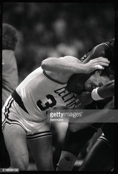 Unidentified 76er holds Celtics' Larry Bird in a headlock during a fight in the third quarter at Boston Garden