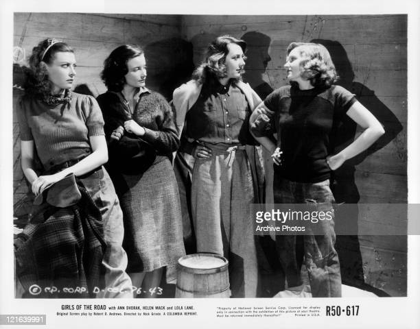 Unidentified actresses watch Ann Dvorak and Lola Lane have a conversation in a scene from the film 'Girls Of The Road' 1940