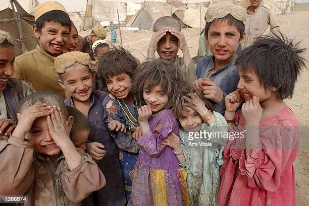 Unidentified Afghan children from the Kuchi nomadic tribe laugh despite the horrible living conditions September 4 2002 in an encamptment near Spin...