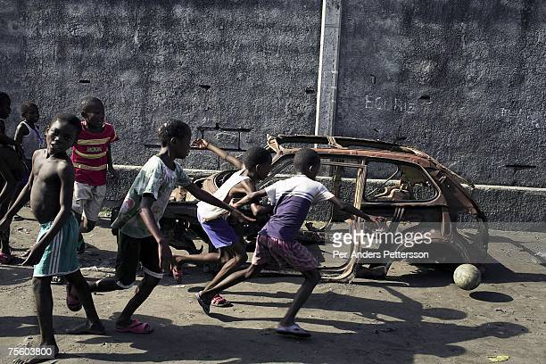 Unidentified boys play soccer next to a burned out car on April 23 2006 in central Kinshasa Congo DRC The area one of the poorest in the capital is...