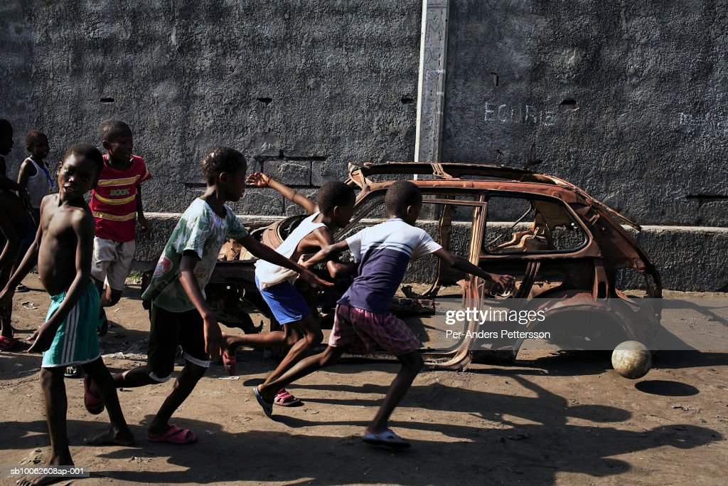 Boy (6-9) playing soccer by wreck of car : Fotografía de noticias