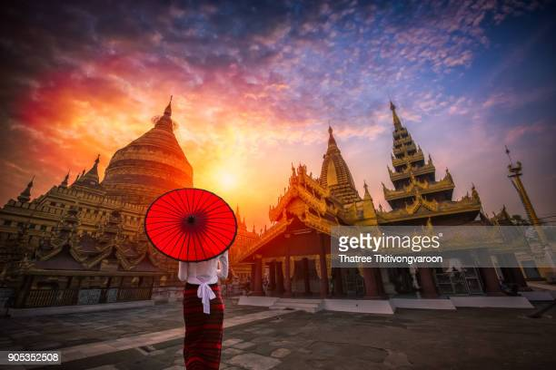 unidentified burmese woman holding traditional red umbrella and looks at golden shwezigon pagoda in bagan, myanmar - myanmar stock pictures, royalty-free photos & images
