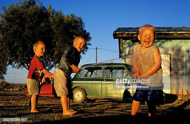 Unidentified children play with a water hose in a garden on September 21, 2003 in Klangelyk, a poor area of Orania, in the Northern Cape province,...