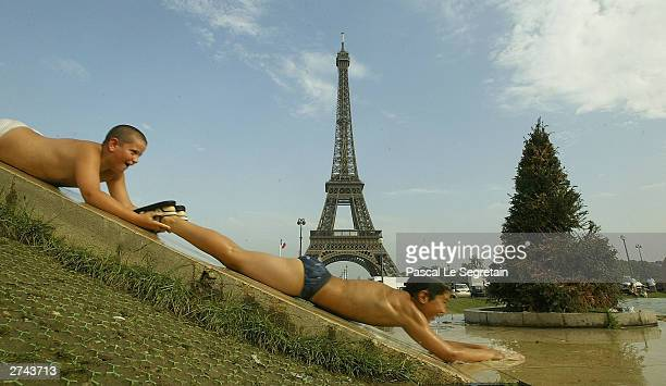 Unidentified children slide into the Trocadero fountains August 13 2003 in Paris The heat has hovered in the mid30s Celsius in many regions of France...