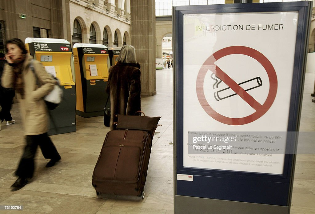 Unidentified commuters walk past an interdiction smoknig sign inside the Eastern railway station on January 31, 2007 in Paris, France. France introduces a smoking ban in public places from February 1, 2007. Bars, restaurants, hotels and night clubs will follow from January 1, 2008.