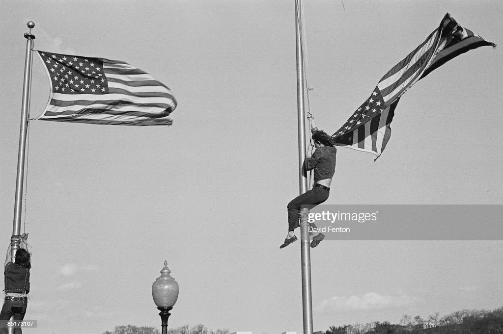 Unidentified demonstrators climb flagpoles to remove the American flag during a massive rally demonstration in opposition to the war in Vietnam and the continued US military presence there, Washington DC, April 14, 1971.