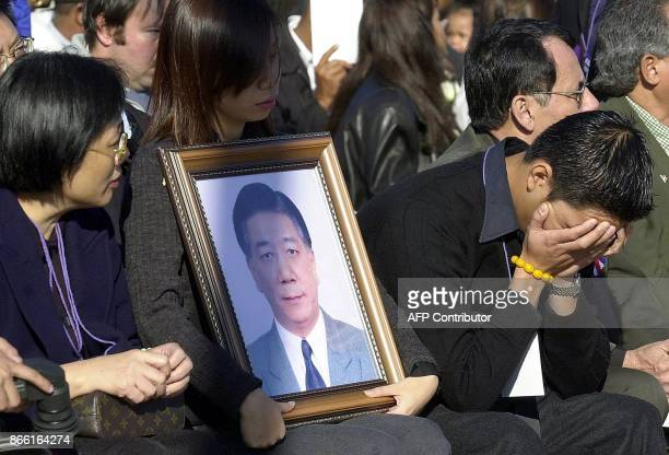 Unidentified family members hold a portrait of a victim of the crash of American Airlines Flight 587 during a memorial service 18 November at Riis...