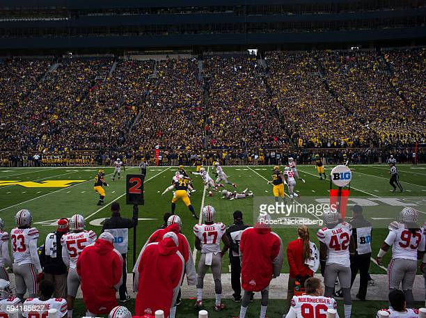 Unidentified fans and alumni of the University of Michigan and Ohio State University foreground cheer their football teams during the traditional Big...