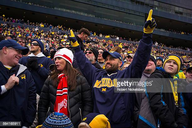 Unidentified fans and alumni of the University of Michigan and Ohio State University cheer their football teams during the traditional Big Ten game...