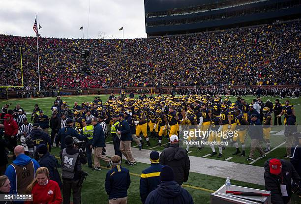 Unidentified fans and alumni of the University of Michigan watch as their team heads off at half time during the traditional Big Ten game over the...
