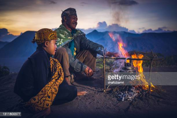 unidentified father and son from cemoro lawang village pose for camera at the mountainside of mount bromo - shaifulzamri stock pictures, royalty-free photos & images
