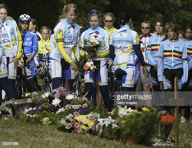 Unidentified female cyclists lay flowers beside a wooden cross at the site of a fatal accident involving some of Australia's top women cyclists near...
