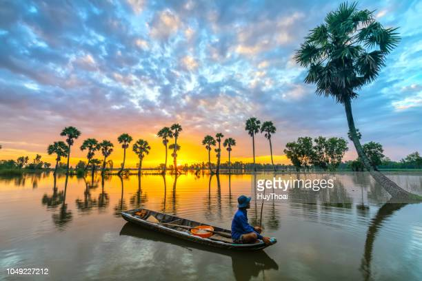 unidentified fishers sit on a boat watching the dawn greeting the new day in his hometown - mekong delta stock pictures, royalty-free photos & images