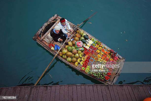 Unidentified fruit seller sells various types of fruits on boat in Halong Bay, Vietnam