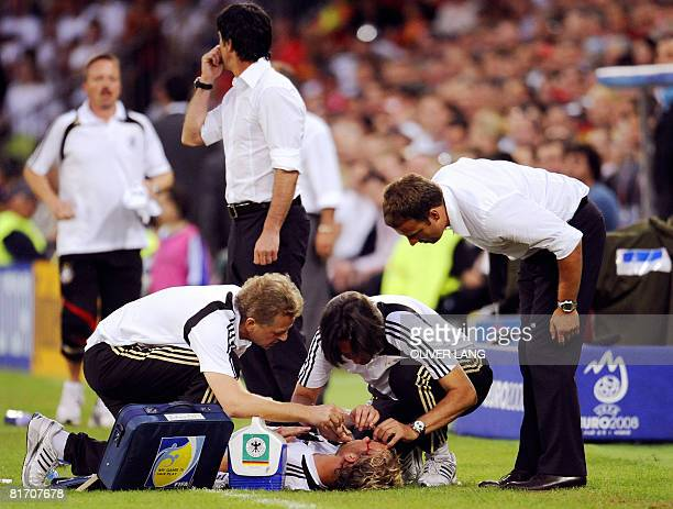 Unidentified German medics attend to the injuries of German midfielder Simon Rolfes as assistant coach of the German team Hansi Flick looks at his...
