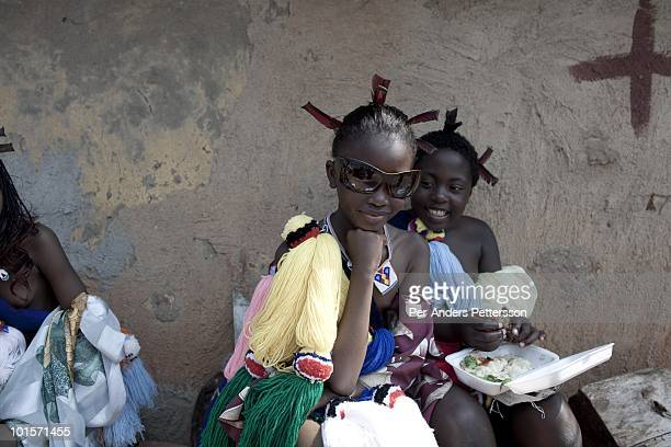 Unidentified girls eat before a traditional Reed dance ceremony at the Royal Palace on August 31 in Ludzidzini Swaziland About 80000 virgins from all...