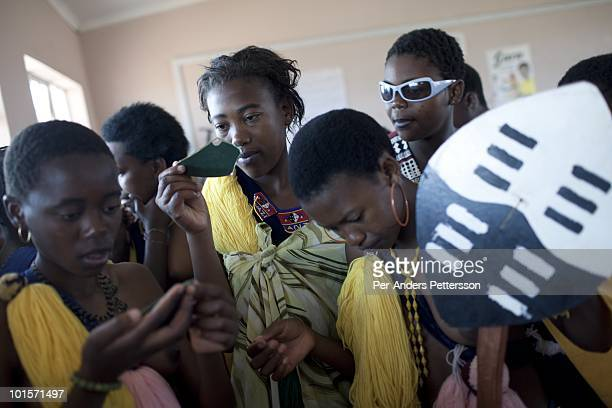 Unidentified girls put on makeup before a traditional Reed dance ceremony at the Royal Palace on August 29 in Ludzidzini Swaziland About 80000...
