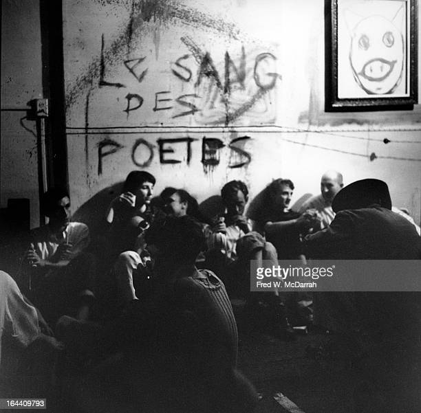 Unidentified guests sit both on a mattress and on the floor at a birthday party for Beat artist Ted Joans New York New York July 25 1959 The text on...