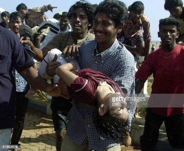Unidentified Indian people carry the dead body of a girl at the Marina beach in Madras, 26 December 2004, after tidal waves hit the region. Tidal...